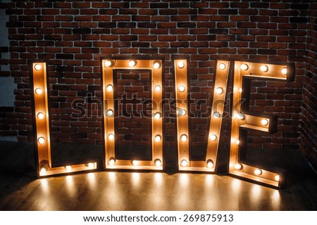 large illuminated letters LOVE in the studio. - stock photo