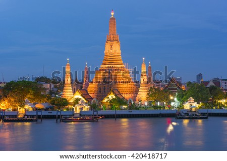 Large illuminated temple Wat Arun after sunset seen accross river Chao Phraya. Bangkok, Thailand - stock photo