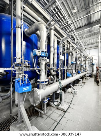 Large industrial boiler room. Blue tanks and shiny metal pipes - stock photo