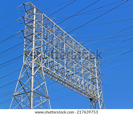 Large industrial electricity transmission tower or electricity pylon steel lattice grid structure, close up view.  - stock photo
