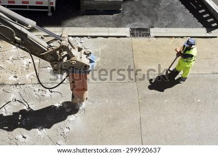 large jackhammer construction vehicle machine destroying pavement of a city street - stock photo