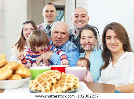 large joyful three generations family sits on sofa in livingroom at home - stock photo
