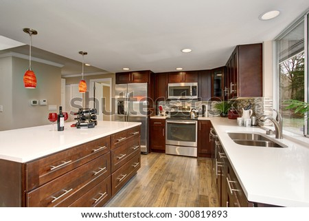 Large kitchen with white counter tops, and a big island. - stock photo