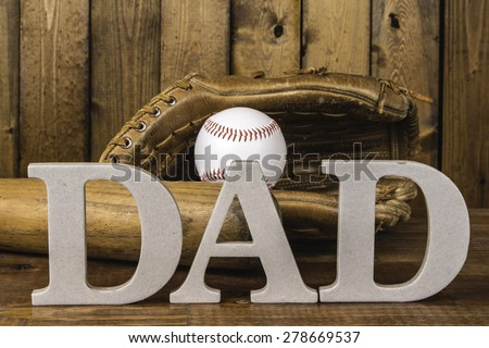 large letters spelling dad in front of baseball bat and baseball in glove - stock photo