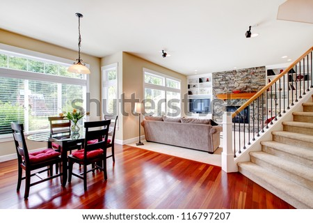 Large living and dining room with staircase, cherry hardwood. - stock photo