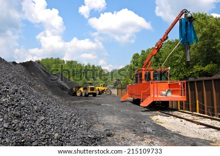 Large Loaders loading a Stock Pile of Coal into Rail Cars - stock photo