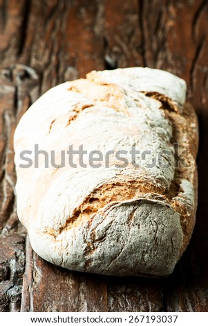 Large loaf of bread on wooden table - stock photo