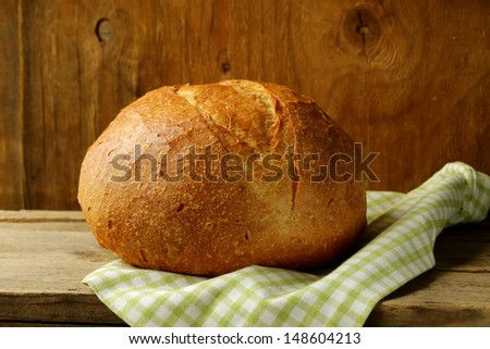 large loaf of homemade bread with a kitchen towel - stock photo