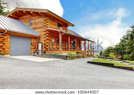 Large log cabin with porch, garage and forest. - stock photo