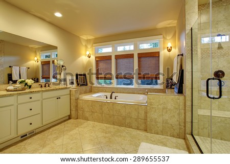 Large master bathroom with tile floor, bathtub, and long mirror. - stock photo