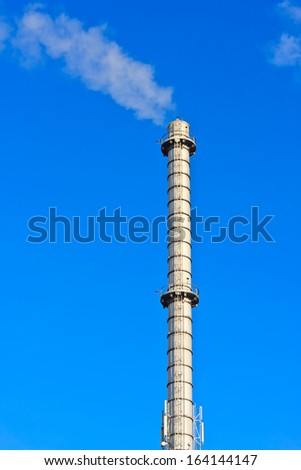 Large metal industrial chimney and smoke - stock photo