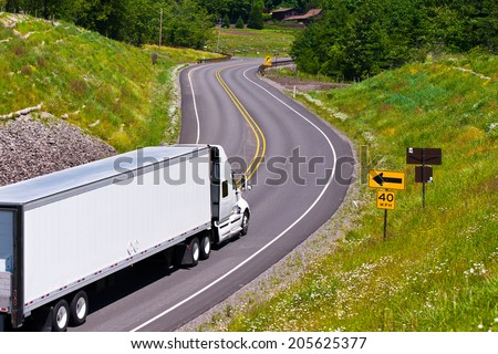 Large modern classic white truck with a trailer carrying commercial industrial cargo on the scenic highway winding among hills covered with trees and separated the safety barrier with road signs. - stock photo