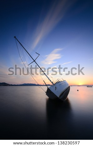 Large modern sailing yacht stranded on a beach after storms in the Mediterranean at sunset - stock photo