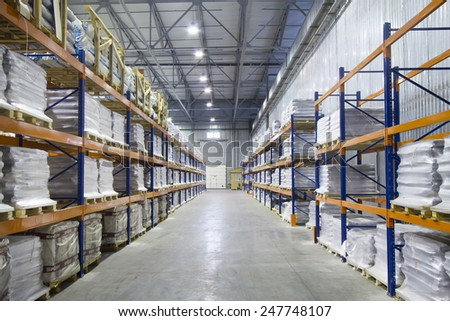 Large modern warehouse. Pallet metal racks with a heavy load. - stock photo