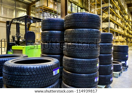 Large modern warehouse with forklifts and stack of car tires - stock photo
