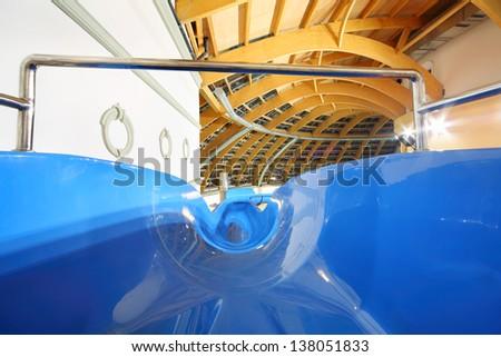 Large multi-colored water slides in indoor aquapark. Descent blue slide. - stock photo
