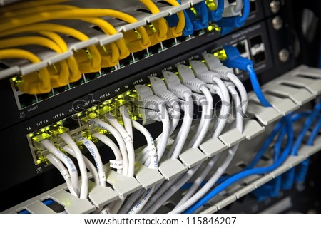 Large network hub and connected Internet cables. Selective focus - stock photo