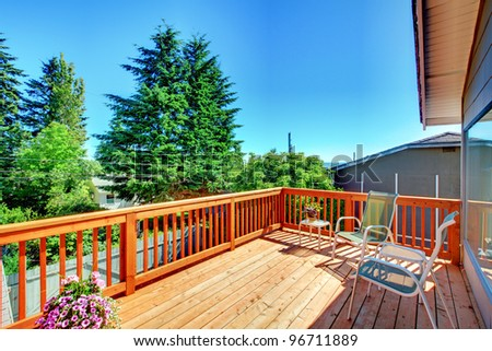 Large new wood deck home exterior with chairs, trees and flowers. - stock photo
