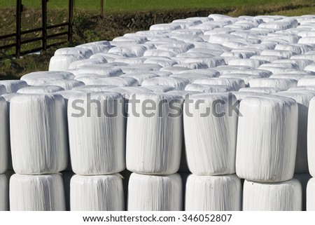 Large number of wrapped bale silages stacked up at the farm - stock photo