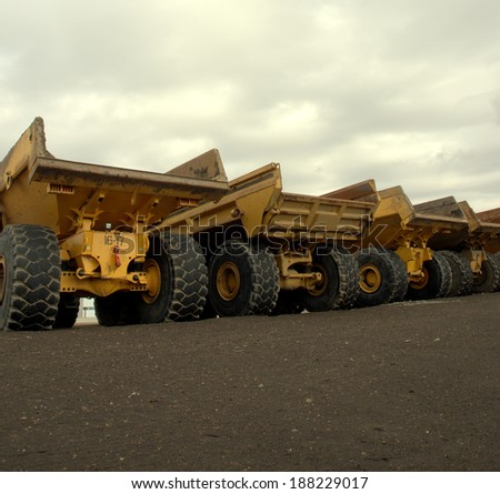 Large off road dump trucks lined up awaiting their next assignment - stock photo