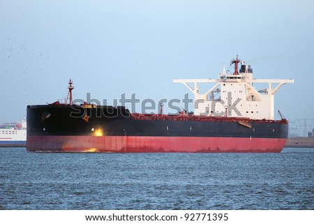 Large oil tanker leaving Rotterdam harbor at sunset - stock photo