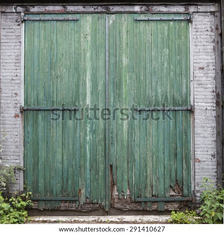 large old barn doors with peeling green paint in white brick wall - stock photo