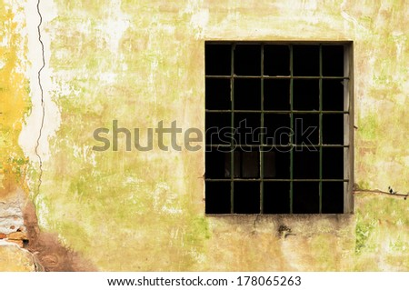 Large old window with broken panes on old cracked wall - stock photo