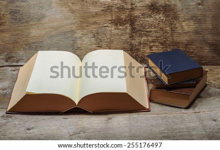 large open book and three small books - stock photo