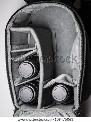 Large open camera bag with three lenses inside - stock photo