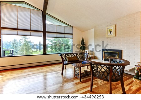 Large open living room with vaulted ceiling, white brick fireplace and hardwood floor. - stock photo