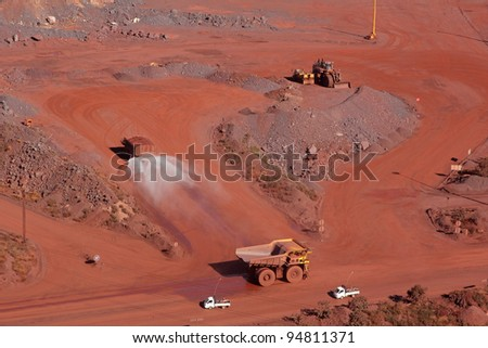 Large, open-pit iron ore mine with trucks - stock photo