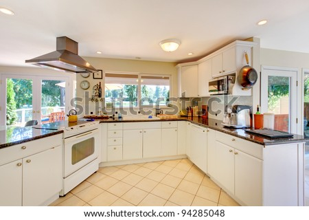 Large open white kitchen with beige floor and lots of windows. - stock photo