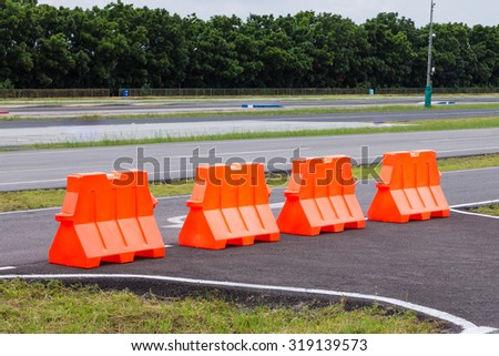 Large orange plastic barrier lined up in rows  - stock photo