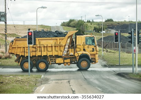 Large Ore Haul Truck with full load crossing a public road South Wales, United Kingdom - stock photo