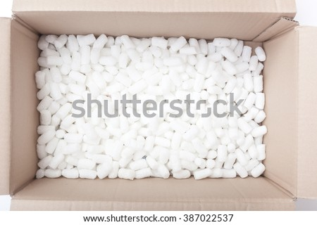 Large packaging box filled with many white styrofoam pellets - stock photo