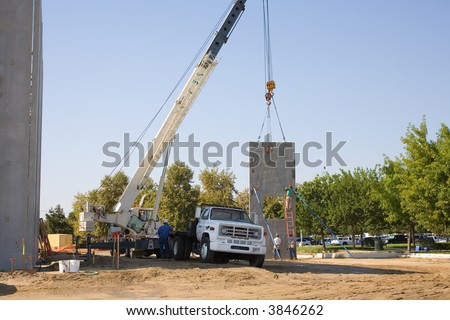 Large panels of precast concrete are tilted up with cranes to form the walls of a large building - stock photo
