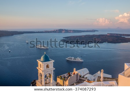 Large panoramic view over the island of Santorini, Greece, and Caldera, as seen from the highest point, the village of Imerovigli, with two large cruise ships anchored in the bay, in the sunrise light - stock photo