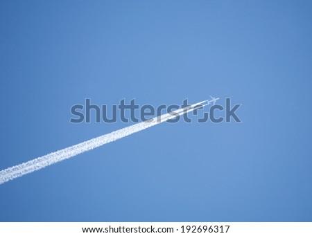 Large passenger jet flying high in clear blue sky, leaving long white trail - stock photo