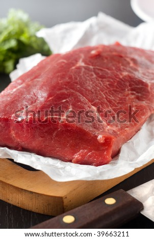 Large piece of uncooked beef lying on the white paper and a knife - stock photo