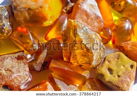 Large pieces of transparent and opaque broken natural amber on white background - stock photo
