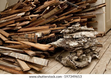 Large pile of hardwood floor being ripped out at an apartment during construction  - stock photo