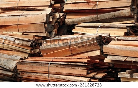 Large piles of hardwood lumber and planks are tied together with steel bands  - stock photo