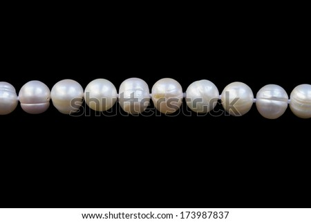 Large pink pearls closeup on black background - stock photo