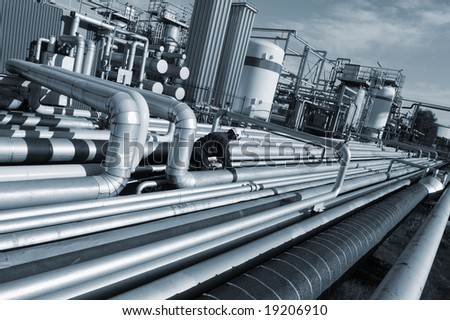 large pipelines construction as seen inside oil and gas industry, engineer at work, blue toning concept - stock photo