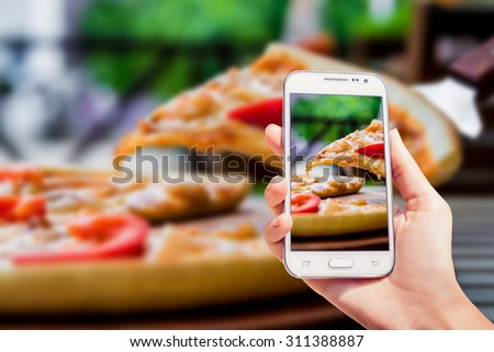 Large pizza on the screen. Phone in the hand. Restaurant - stock photo