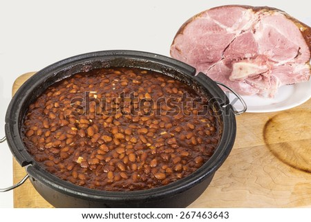 Large Pot of Sweet Southern Style Baked Beans with Baked Pork Shoulder in background on rustic wooden cutting board with neutral background. - stock photo