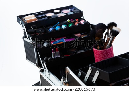 Large professional makeup container with containers tubes lipsticks eyeshades and makeup brushes - stock photo