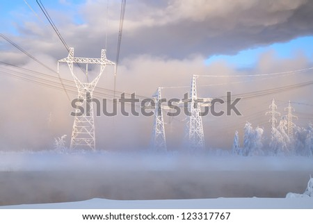 Large pylons of an electric main on a frost in the sun before sunset, Russia, Siberia - stock photo