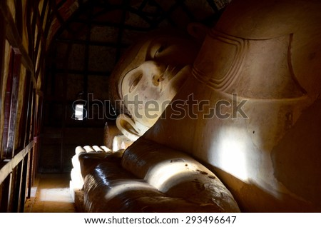 Large Reclining Manuha Buddha at Shinbinthalyaung Temple in Ancient City in Bagan (Pagan), Myanmar with over 2000 Pagodas and Temples. - stock photo