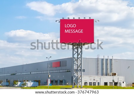Large red billboard and Aluminum facade in front of industrial building with blue sky. Logo Message. - stock photo